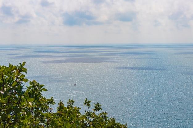 Анапа, россия - 11 июня 2021 года: каменистый пляж побережья черного моря в деревне большой утриш, полный людей в яркий солнечный летний день. с высоты птичьего полета.