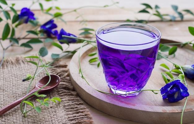 アンチャンフラワージュースまたはブルーピーフラワーハーブティー、木製テーブルに木のスプーンでガラスカップの蝶エンドウ豆