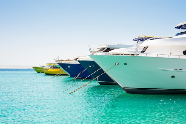 Anchored big yachts and sailboats on a turquoise water.
