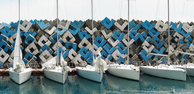 바다 항구의 방파제 배경에서 레가타를 위한 정박된 범선