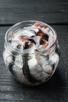 Рыбные консервы из анчоусов в жестяной банке с морепродуктами, в стеклянной банке, на черном фоне деревянного стола