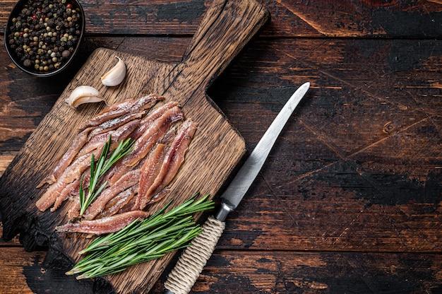 Маринованное филе рыбы анчоусы на деревянной доске. темный деревянный фон. вид сверху. скопируйте пространство.