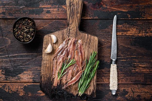 アンチョビは木の板に魚の切り身を漬けました。暗い木製のテーブル。上面図。