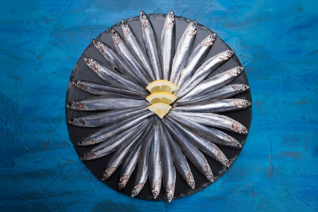 Anchovies in the shape of a circle on a black stone. seafood. small sea fish