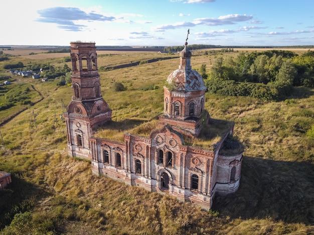 Древняя заброшенная и разрушенная церковь, освещенная заходящим солнцем.