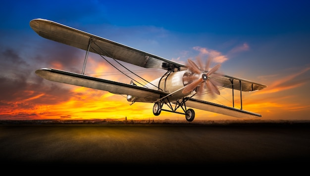 Ancient airplane take off from the airport runway on sunset background Premium Photo