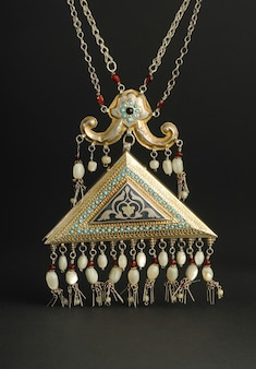 Ancient antique pendant with stones on black background. middle-asian vintage jewelry
