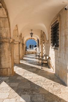 Perast의 산책로에있는 오래된 집에있는 고대 아치형 통로. 몬테네그로.