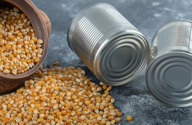 An ancient bowl full of uncooked popcorn seeds with metallic cans.