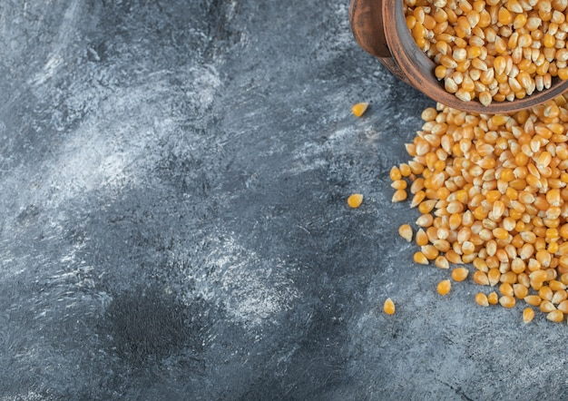 An ancient bowl full of uncooked popcorn seeds.