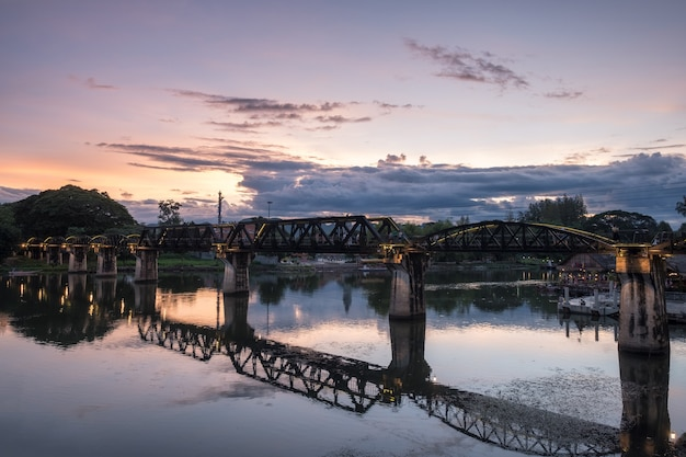 Ancient bridge on river kwai history of world war ii in evening at kanchanaburi, thailand