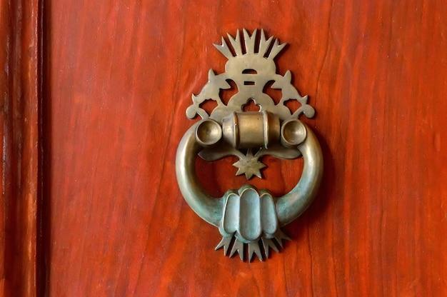 木製の表面にオリエンタルスタイルの古代ブロンズハンドル