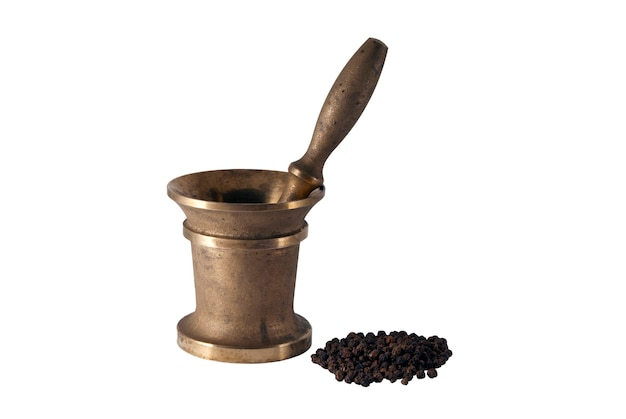 Ancient bronze mortar and a handful of black pepper peas on a white background