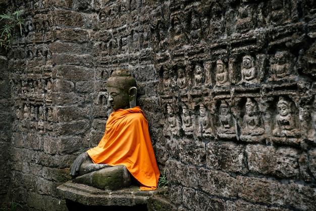Древняя статуя будды в оранжевой обложке