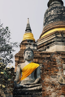 Ancient buddha statues placed on brick walls in thai temples.