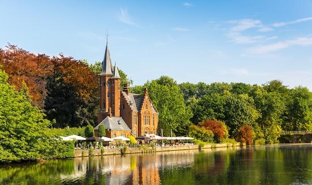 Старинное здание с башней в зеленом парке, старом европейском городке.