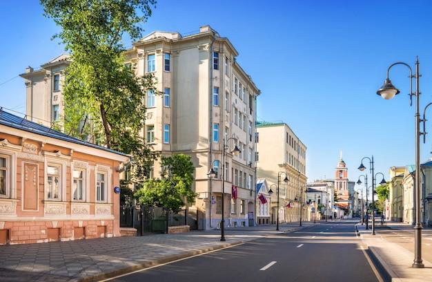 Старинные здания и колокольня троицкой церкви на пятницкой улице в москве в лучах утреннего летнего солнца