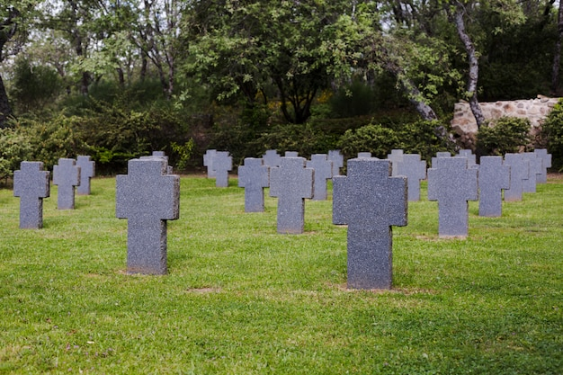 Ancient cemetery with grey cross tombs over a green field. outdoors a city or town. death concept