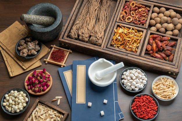 テーブルの上の古代漢方薬の本とハーブ