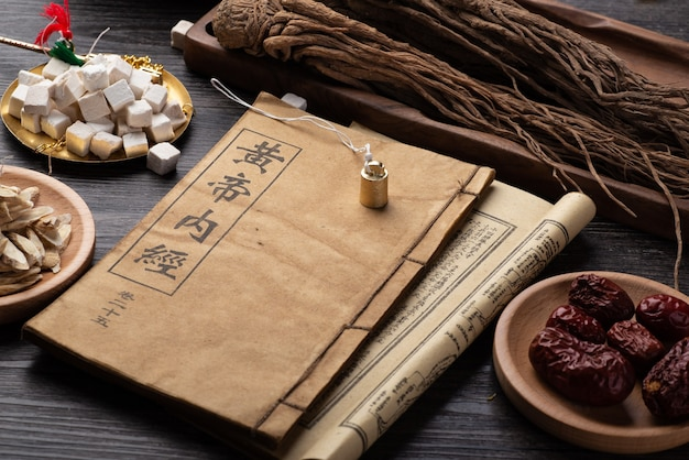 Ancient chinese medicine books and herbs on the table