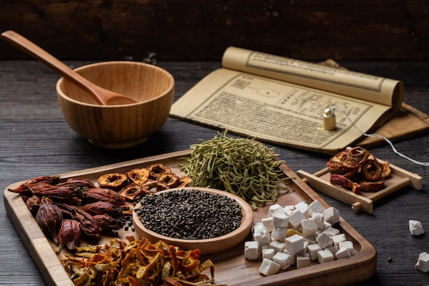 Ancient chinese medicine books and herbs on the table.