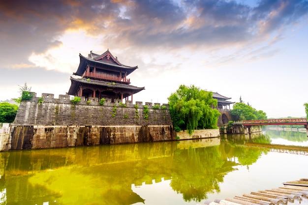 Древняя городская стена у реки с видом на закат