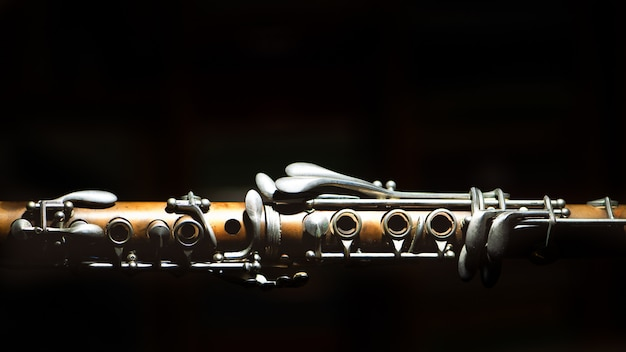 Ancient clarinet. detail on a black background