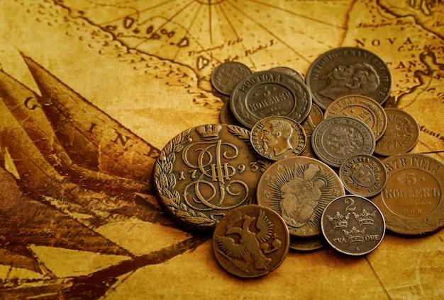 古代のコイン。旧世界地図上のロシアとヨーロッパ諸国の金属マネー。