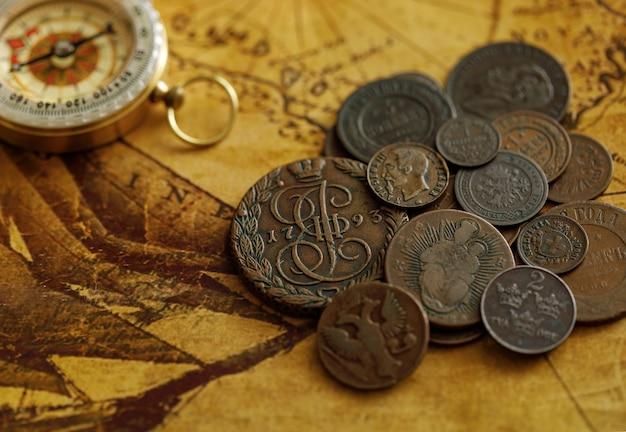 コンパス付きの古代のコイン。旧世界地図上のロシアとヨーロッパ諸国の金属マネー。コレクション。
