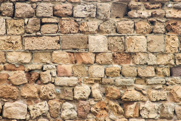 Ancient collapsing brick wall close up as background