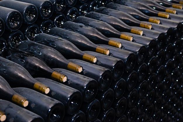 Ancient dark dusty wine bottles aging in underground cellar in rows