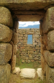 Ancient doorway with the remains of the inca and the mountain ranges, machu picchu, cusco, peru