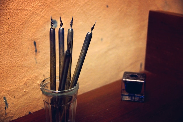 잉크병 옆 탁자에 있는 고대 깃털 펜, 벽에 얼룩 흔적