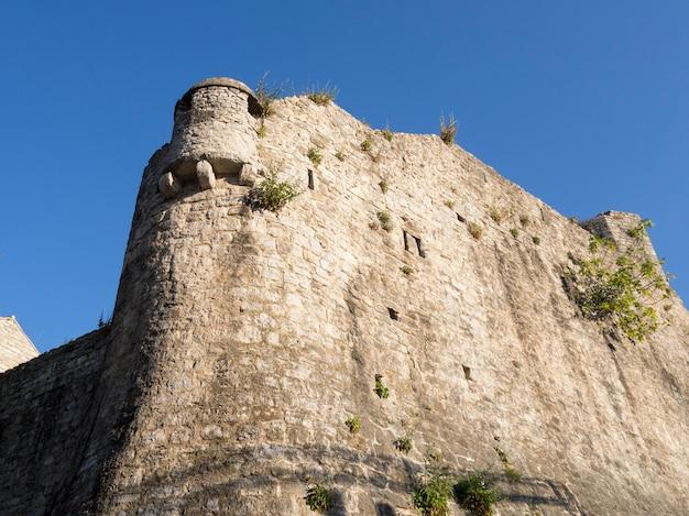 Древняя крепостная стена с зелеными растениями в старом городе будвы в черногории