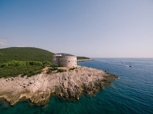 바다 조감도 옆 녹지 사이의 바위 해안에 있는 고대 요새