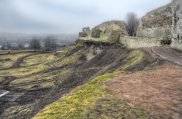 Древняя крепостная стена в изборске (псков) с башнями в пасмурный туманный осенний день