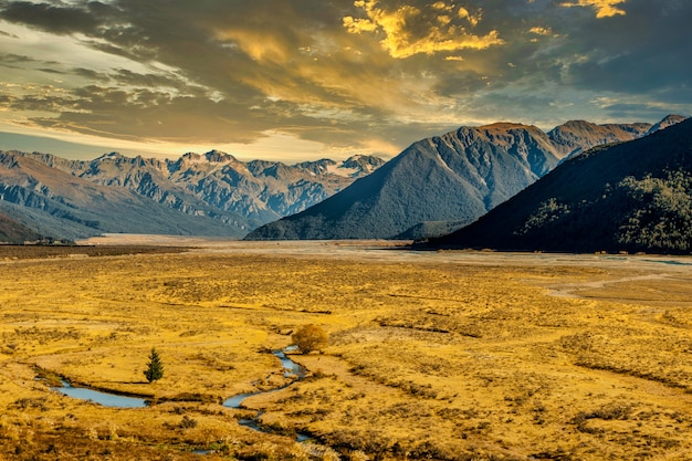 Ancient glacial valley floor shrouded by late afternoon sunlight with the magnificent southern alps in the distance