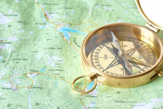 地図上の古代の黄金の羅針盤。旅行のコンセプト