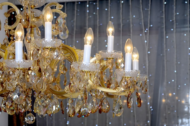 An ancient hanging retro chandelier with built-in lamps for electric lighting