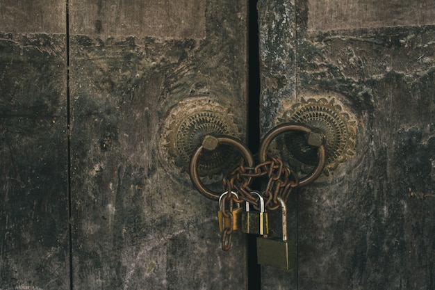 Ancient house door locked with modern keys background