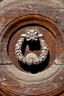 Ancient italian door handle on brown wooden background.