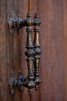 Ancient italian metal door handles on brown wooden door.