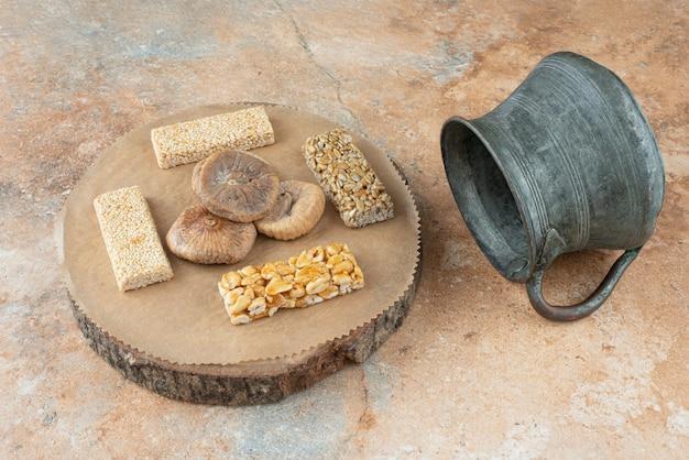 Древний чайник и арахисовые ломтики на мраморном фоне