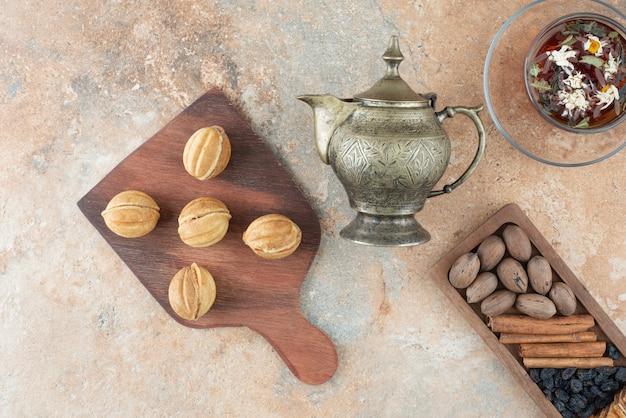 Bollitore antico e biscotti rotondi dolci su fondo di marmo