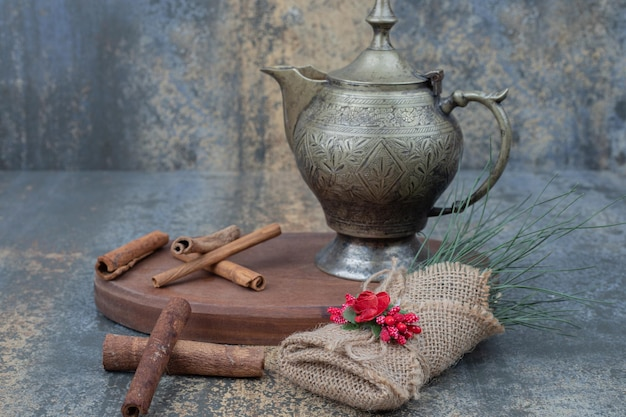 Ancient kettle with cinnamon sticks on wooden plate.