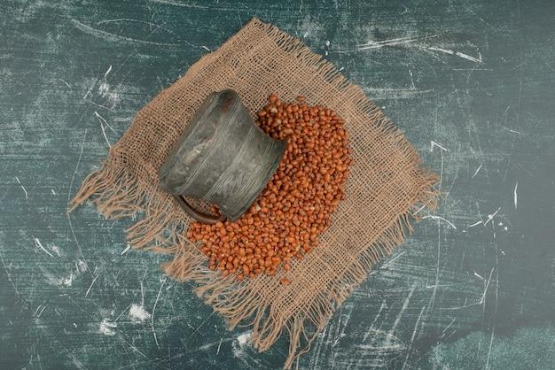 大理石の表面の黄麻布に小麦と古代のやかん