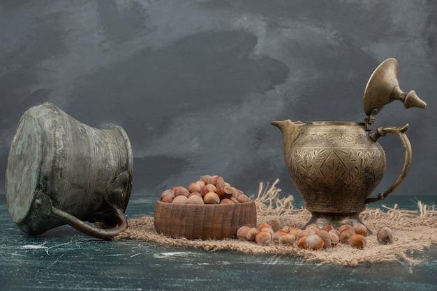 Древний чайник с деревянной тарелкой орехов на мраморном фоне