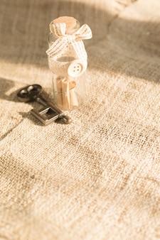 Древний ключ и сообщение прокрутки в бутылке с белым фоном мешковины. концепция фона для дня святого валентина.