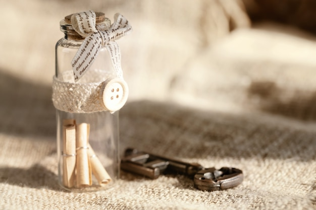 Ancient key and scroll message in the bottle with the white burlap background.concept background for valentine's day.