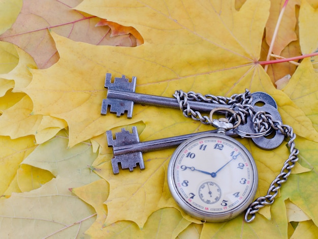 Ancient keys and a pocket watch lie on yellow maple autumn leaves